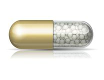 Medical golden capsule with granules Stock Photo
