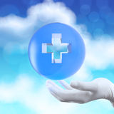 Medical hand with globe select on first aid sign Royalty Free Stock Images
