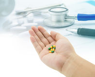 Medical, hand holding capsule pills, stethoscope, pills royalty free stock image
