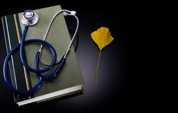 Medical handbook with stethoscope and ginkgo leaf of traditional medicine. Medical book with stethoscope and ginkgo leaf symbol of traditional medicine on Royalty Free Stock Photos