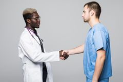 Medical handshake. Doctoral meeting. Two confident doctor and surgeon standing on gray and shake their hands. stock images
