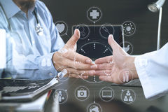 Medical and health care concept,Doctor and patient shaking hands. In modern office at hospital with virtual computer interface graphic and icons diagram Stock Photos