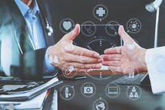 Medical and health care concept,Doctor and patient shaking hands. In modern office at hospital with virtual computer interface graphic and icons diagram Stock Photography