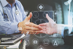 Medical and health care concept,Doctor and patient shaking hands. In modern office at hospital with virtual computer interface graphic and icons diagram Royalty Free Stock Photo