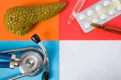 Medical or health care design concept photo-organ pancreas, diagnostic medical tool stethoscope and medications pills and via royalty free stock images