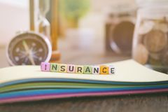 Medical and health care management concept word block INSURANCE on yellow book Stock Photo