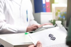 Medical and health care prices concept. Patient holding paper document, insurance, bill or invoice with dollar sign in doctor office in hospital or emergency Stock Photos