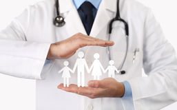 Medical health insurance concept. Doctor with family symbol in hands Royalty Free Stock Photo