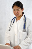 Medical Healthcare Doctor. A beautiful female medical healthcare doctor wearing a stethoscope and using a computer laptop Stock Photos