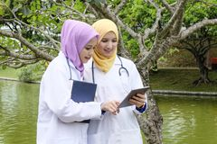 Young muslimah doctor standing and having discussion at park during lunch hour. Stock Images