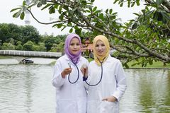 Young muslimah doctor standing and having discussion at park during lunch hour. Stock Photos