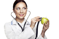 Medical and healthy lifestyle concept. Attractive happy female doctor holding green apple and stethoscope and smiling Stock Photo