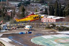 Medical helicopter landing. Yellow service medical elicopter landing in winter Stock Image