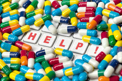 Medical Help Needed. A keyboard with help written on its keys covered by colorful pills Royalty Free Stock Image
