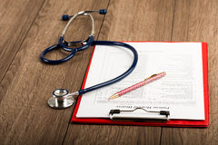 Medical history with stethoscope and pen Stock Photography