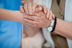 Medical home care for elderly people. Caring nurse holding old woman hands Stock Photos