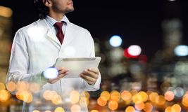 Medical industry concept by means of successful doctor. Double exposure of confident doctor in white sterile coat and night modern cityscape view on background Royalty Free Stock Image