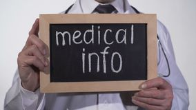 Medical info text on blackboard in doctor hands, consultation with therapist. Stock footage stock video footage