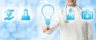 Medical Innovation Concept - Doctor with Lamp Icon. Medical Innovation Concept - Doctor points at lamp or light bulb icon with other medical icons showing symbol Royalty Free Stock Photos