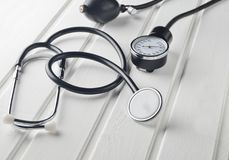 Medical instrument for measuring pressure. Stethoscope on a white wooden table. Cardiovascular diagnostics Royalty Free Stock Images