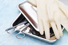 Medical instruments. Scalpel and clamp in a steel tray with a cover. Medical rubber gloves Royalty Free Stock Photos