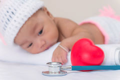 Medical instruments stethoscope with heart and baby girl Royalty Free Stock Photos