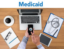 Medical insurance and Medicaid and stethoscope. Doctor working at office desk and using a mobile touch screen phone, computer and medical equipment all around Royalty Free Stock Image