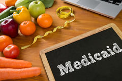 Medical insurance and Medicaid and stethoscope. Fruit and tape measure on a wooden table, top view Stock Photos