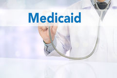 Medical insurance and Medicaid and stethoscope. Medicine doctor hand working on virtual screen Royalty Free Stock Image