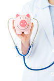 Medical insurance, piggybank with stethoscope Stock Photos