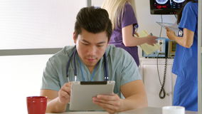 Medical intern in hospital lounge using tablet pc  Royalty Free Stock Photo
