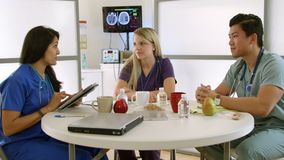 Medical interns in hospital break room with tablet. Medical interns or nursing students in a hospital break room talk happily about what they see on an stock footage