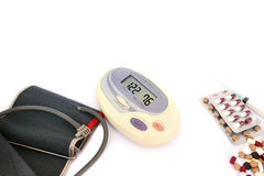 Medical items. Modern digital blood pressure measurement and pills, tablets  isolated on white background Royalty Free Stock Photography
