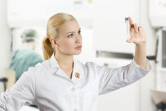 The medical lab. Blond and young nurse making a medical analysis and looking at a test tube stock images