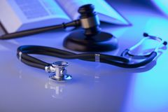 Medical law concept. Place for typography. Gavel, book, stethoscope on glass table, blue light. Place fort text Stock Image