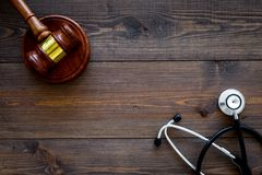 Medical law, health law concept. Gavel and stethoscope on dark wooden backgound top view copy space royalty free stock images