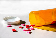 Medical love cure. A medicine bottle spills out love pills in the shape of hearts in red and pink Stock Image