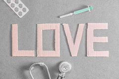 Medical love. A stethoscope, pills and a disposable syringe on a dark background with the word love made out of cardboard for your concepts about medical Royalty Free Stock Image