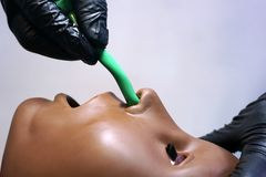 Medical manipulation for airway management. Nasopharyngeal tube airway insertion by stuff in a black gloves on a simulation. Mannequin dummy during medical royalty free stock photo