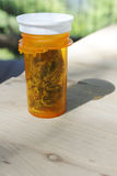 Medical Marijuana. Clear orange brown pill bottle with white lid holds medical marijuana buds on a wood table outside in nature on a sunny day royalty free stock photography