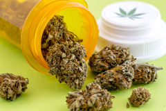 Medical Marijuana Buds and Seeds. Medical marijuana buds spilling out of prescription bottle with branded lid on green background royalty free stock photography