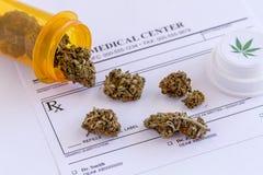 Medical Marijuana Buds and Seeds. Medical marijuana buds spilling out of prescription bottle with branded lid onto blank medical prescription pad stock image