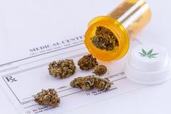 Medical Marijuana Buds and Seeds. Medical marijuana buds spilling out of prescription bottle with lid onto blank medical prescription pad stock images