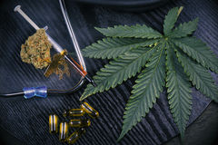 Medical marijuana products with cannabis leaf on black. Medical marijuana products including cannabis leaf, dried bud, shatter piece, cbd caps and hash oil over Royalty Free Stock Photography