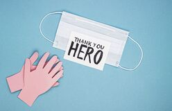 Medical mask, applauding paper hands and the inscription thank you hero on a blue background