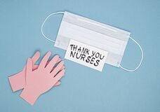 Medical mask, applauding paper hands and the inscription thank you nurses on a blue background