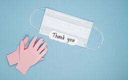 A medical mask, applauding paper hands, and a thank you sign on a blue background