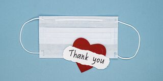 Medical mask, a red heart and the words thank you on a blue background