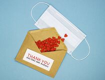 Medical mask with red hearts spilled out of the envelope and the inscription thank you doctors and nurses