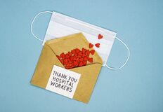 Medical mask with red hearts spilled out of the envelope and the inscription thank you to medical workers